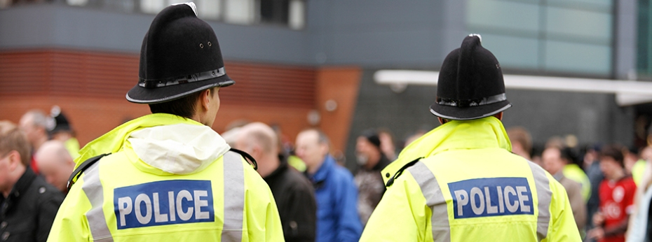 Two Britisih Policemen in Traditional Helmets on Crowd Control